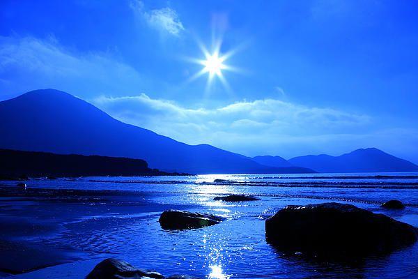 The sun takes on a star shape over a blue beach landscape. County Kerry, Ireland.