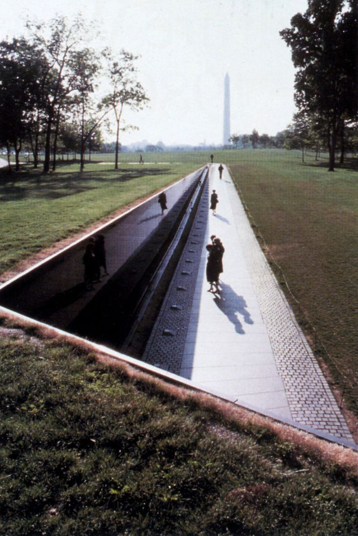 """Maya Lin. Vietnam War Memorial, 1982. When a visitor looks upon the wall, his or her reflection can be seen simultaneously with the engraved names, which is meant to symbolically bring the past and present together. The selected design was very controversial, in particular its unconventional design, its black color and its lack of ornamentation, especially among veterans. Many publicly voiced their displeasure, calling the wall """"a black gash of shame."""""""