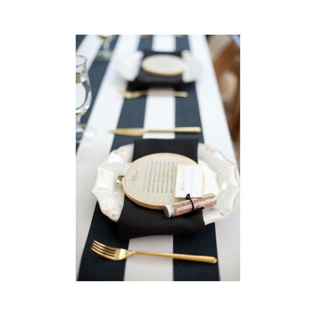 Couverts or sur nappe noir et serviettes blanches
