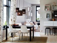 Comedor mediano con una mesa en negro-marrón, con capacidad para seis personas, y cuatro sillas blancas con forma anatómica y patas cromadas.