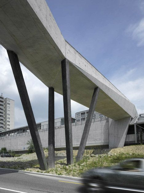 Faceted concrete bridge by 2b Architectes links a metro station with a forest.