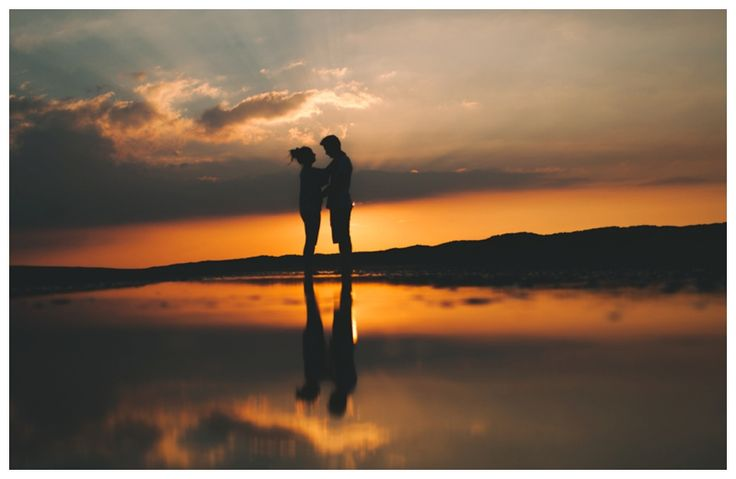 Silhouette of couple at sunset on the beach reflection in the water. www.ellen-richardson-weddings.com/blog
