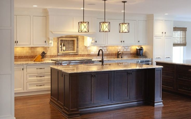 """This traditional kitchen with modern features was part of an addition in Ladue, MO. Notice the inset painted cabinetry in soft cream which compliments the cherry cabinetry in coffee with ebony glaze. The countertops on the perimeter and the island are in white spring with ogee edge. The Brizo plumbing fixtures are in oil-rubbed bronze. Top-of-the-line appliances include a 48"""" Wolf range with double griddle, Sharp microwave and warming drawers and a Sub-zero Refrigerator."""