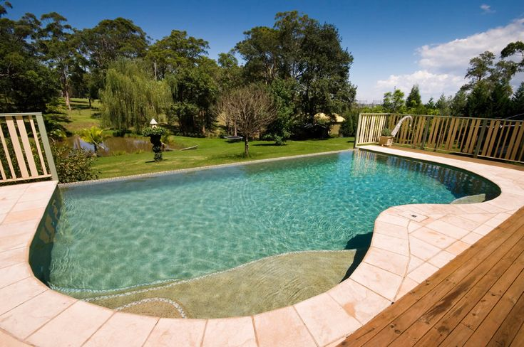This simple B shaped saltwater swimming pool is made more dramatic by the rural backdrop and a blade edge on one side creating a wet-edge effect.