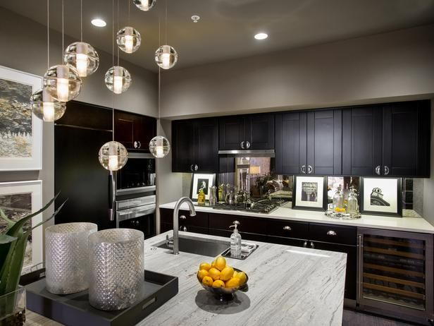 A glass backsplash visually expands the space while the quartz-topped galley-style countertop provides display space for photography: black-and-white snapshots of Boston attractions.