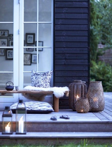 black paint, faded cedar deck, with warm wood tones ... LOVE the lanterns, the combo of the rectangular glass/metal with the oversized willow/reed basket hurricane lanterns in different sizes/shapes/styles of weaving: