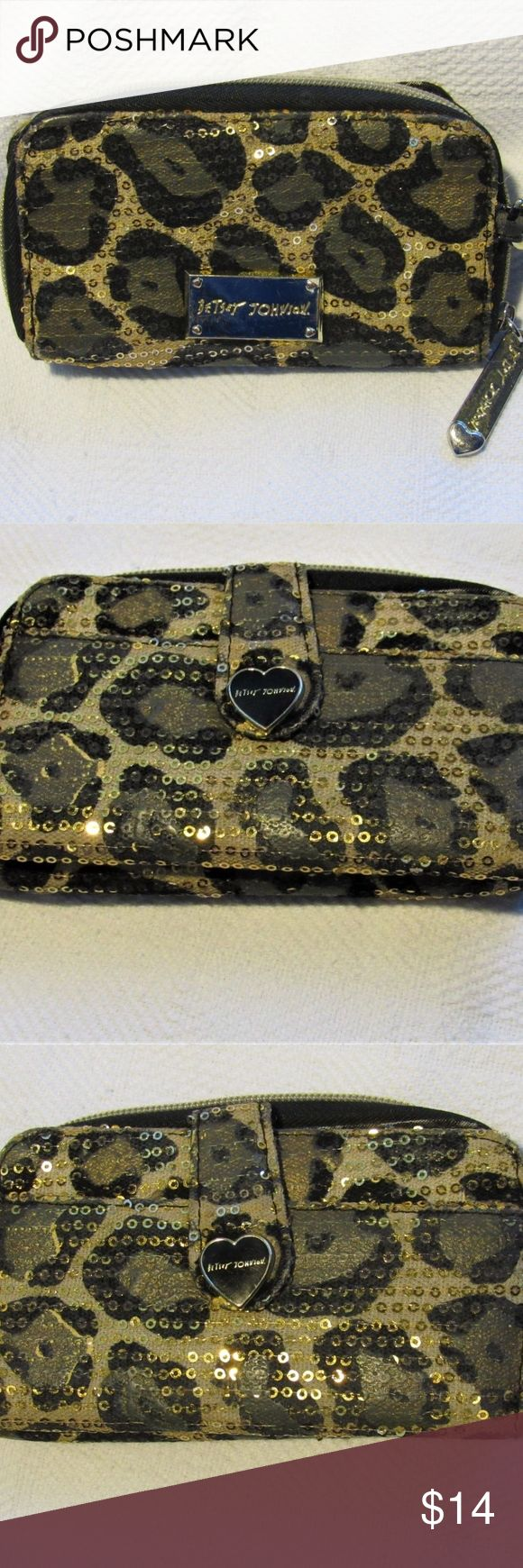 """Betsey Johnson Animal Print Sequin Zip Up Wallet Betsey Johnson Animal Print Zip Up Wallet Gold Sequins.  In good pre-owned condition. Details:   Black/Gold Sequin Zip Closure Change Compartment Gold-tone Betsey Johnson Logo Plaque on Front Logo Print Lining Open Compartment on other Side of Change Compartment with 1 slip pocket and 5 Credit Card Slots Exterior slip pocket under snap closure Measures Approximately 6"""" W x 3.5"""" H x 1"""" D  From a Smoke Free/Pet Free Home Betsey Johnson Bags…"""