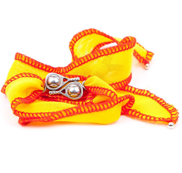 Pulsera Dejada. Pulsera  de seda tailandesa ribeteada en color amarillo con los bordes rojos e insignia en plata de ley envejecida.