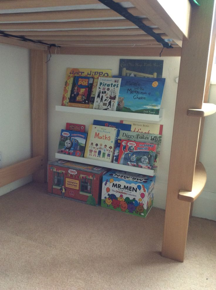 IKEA Ribba picture ledges used to create bookshelves and a mini reading corner under a mid sleeper bed.