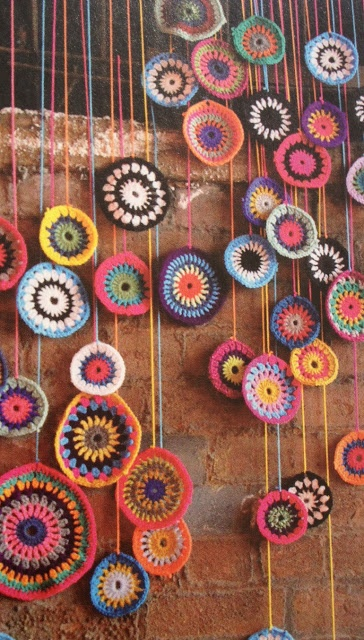 I can't see myself spending this much time crocheting- but something similar out of paper, painted wood circles or recycled sweaters could make a good backdrop.