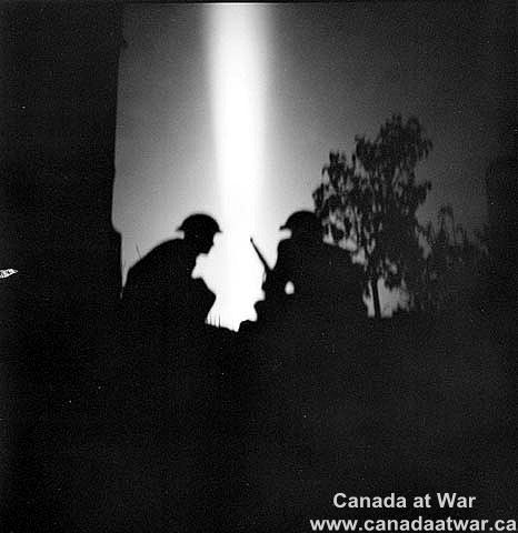 Normandy - Operation Spring - Soldier silhoutted against gun fire, Fleury sur Orne, France, early morning, 25 July 1944.