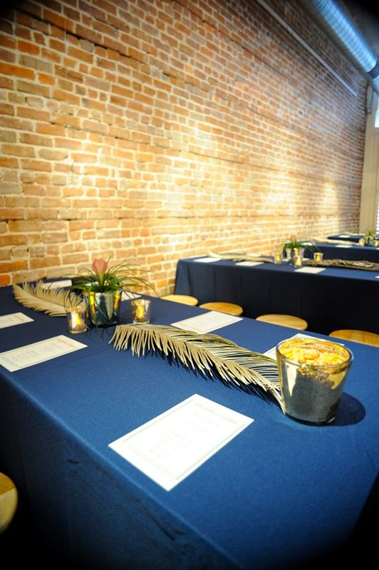 Our centerpieces were: Spraypainted sago palm leaves, inexpensive votives, and plants from Ikea. So that the back of the room could see the ceremony, half of the table were bar height using table leg extenders and bar stools. (photo by angelamericaelza.com)