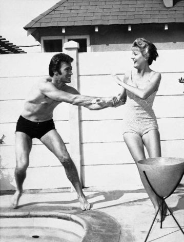It s not all work and no play for one of TV s busiest actors, Clint Eastwood who plays the role of Rowdy Yates on the CBS-TV  Rawhide  series. Away from the studio he finds rest and relaxation, fun and frolic at his home in Hollywood, April, 19, 1960. Here, his wife Maggie refuses Clint s invitation to try the water in the swimming pool outside their Hollywood home. Photo: (AP Photo) / BE
