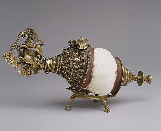 A nineteenth-century Indian sankh/conch shell; symbols incorporated into its adornment include nagas (serpent divinities), kirtimukhas ('faces of glory'), a yoni, symbol of female energy,, a makhara (monster), yali (monster), a lingam/yoni, symbol of Shiva and unified male/female force; Ganesh, and Nandi. (Metropolitan Museum of Art)