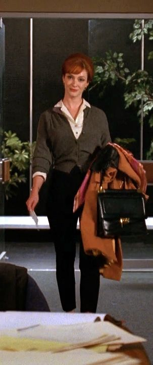 There's something creepy about this woman, but I like this outfit. White blouse, charcoal sweater, black slacks, over large black purse, and brown overcoat.