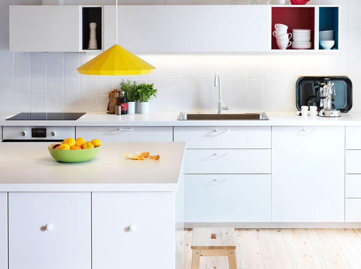 Modern IKEA kichen with white doors, drawers and worktops and coloured open cabinets