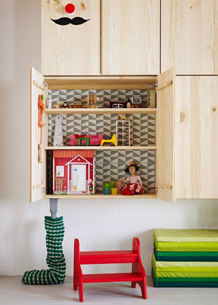 IKEA storage cabinets on a wall. One is open with dolls house furniture inside.