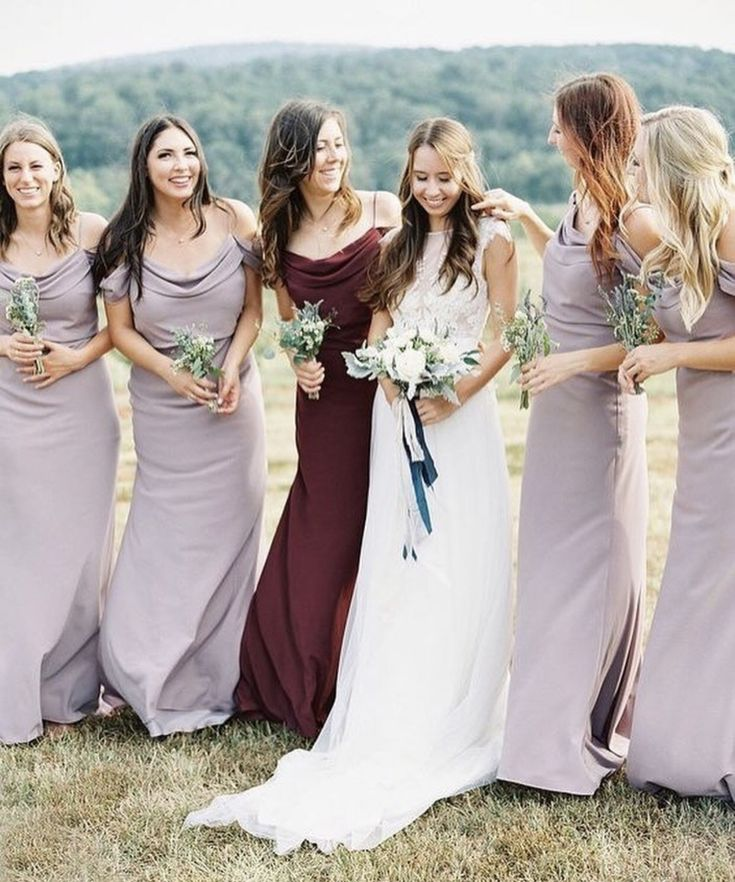 Jenny Yoo Bridesmaids, in our Sabine dress in light purple and the maid of honor in burgundy. The Sabine dress comes in our elegant Crepe De Chine fabric. It has a pleated cowl neck for dramatically stunning effect and pleated, draped, off-the-shoulder straps. The floor length bias cut skirt creates a romantic, modern look while the fit and flare skirt elongates and highlights curves and flatters the figure. It is fully lined with a center back zipper. Photo by Wedding Sparrow.