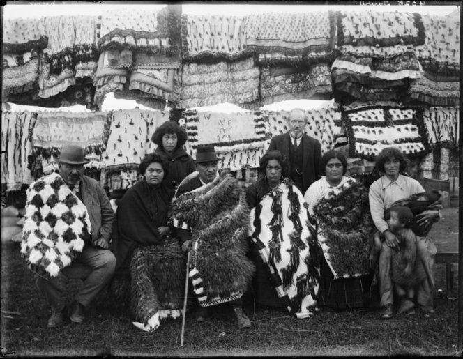 Unidentified Maori group (from the Tauri family?), and a Pakeha man, alongside rows of Maori cloaks, and quilts, circa 1910. Possibly at a tangi.