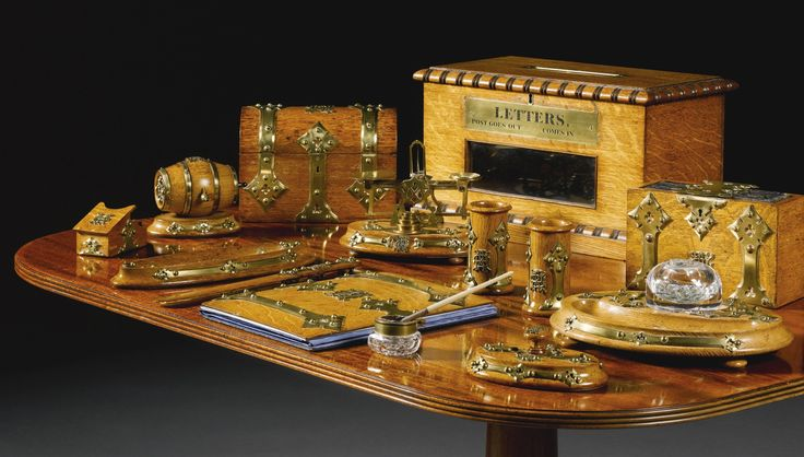 A Victorian oak and brass-bound desk set circa 1850 comprising a domed stationary casket, a paperweight, an oval pen tray, a letter opener, a blotter, a set of postal scales with four weights, a house letter box, an ink stand with pen tray and glass inkwell ( defective), two quill vases, a nib cleaner, a string container in the form of a barrel and four leather bound ledgers in a lockable case, monogrammed AEH, some pieces bearing a paper label for ORTNER & HOULE/LONDON/3 ST JAMES ST