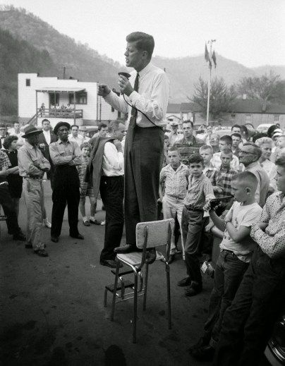 La campagna di John F. Kennedy nelle zone rurali del West Virginia, precariamente arroccato su un seggiolone per fare il suo discorso, 1960