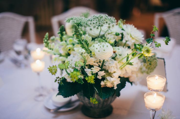 Low and lush table arrangement of white hydrangea, white ranunculus, snapdragon and dahlia, Queen Anne's lace, maiden hair fern and bupleurum in a mossed concrete urn.