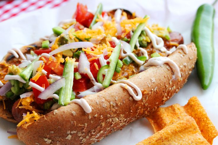 Jalapeño Chili Dog  -2 cups Chili   2 Hot Dogs   2 Hot Dog Buns   1 Tomato (medium size)   2 Jalapeno or Serrano Hot Peppers   3 tablespoons chopped Red Onion   1 cup shredded Cheddar Cheese   1 Avocado   2 tablespoons Sour Cream   1 tablespoon Salsa