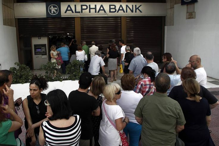 People queue to withdraw money from an ATM outside a branch of Greece's Alpha Bank...
