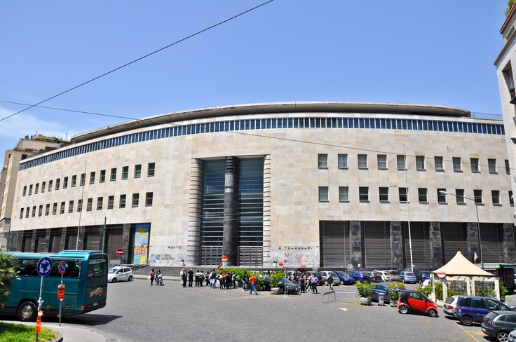 SIGHTS. Palazzo Delle Poste. Looking like a giant, graffitied UFO, Naples' main post office is a striking Fascist concoction. Product of an urban renewal programme that wiped out the San Giuseppe quarter, it was designed in 1935 by Giuseppe Vaccaro and features a number of Fasci