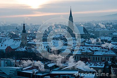 City of Cluj-Napoca, in Transylvania, seen from above in a cold morning. The towers of the churches dominate the cityscape. There is snow on the rooftops and steam and smoke coming out of the chimneys.