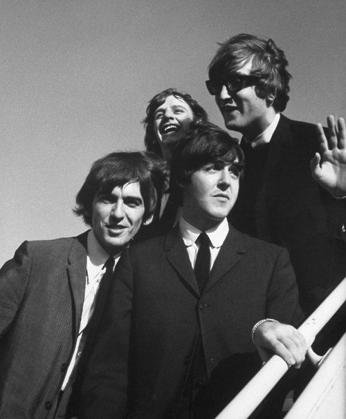 The Beatles wave to fans as they arrive at the Los Angeles airport for a press conference in August 1964.