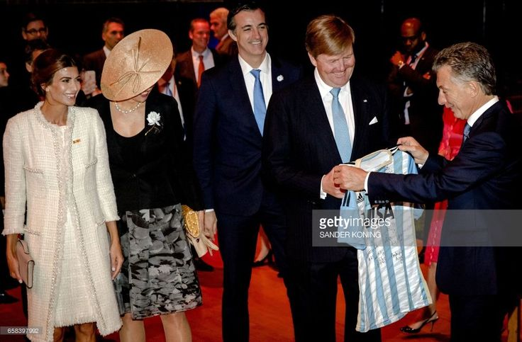 Argentinian President Mauricio Macri (R) gives a football jersey to Dutch King Willem-Alexander (2nd R) during a visit with his wife Juliana Awada (L) and Dutch Queen Maxima (2nd L) at the Beurs van Berlage in Amsterdam on March 27, 2017. / AFP PHOTO / ANP / Sander Koning / Netherlands OUT