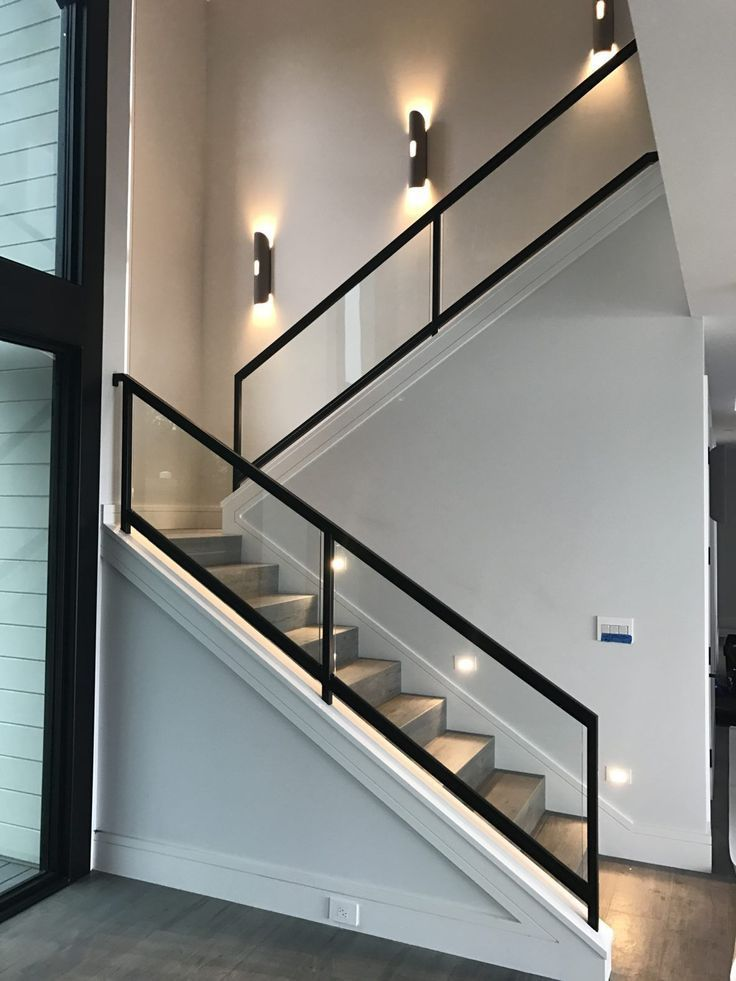 Steel and wooden stairs with a glass handrail lead to the second floor this … #WoodWorking