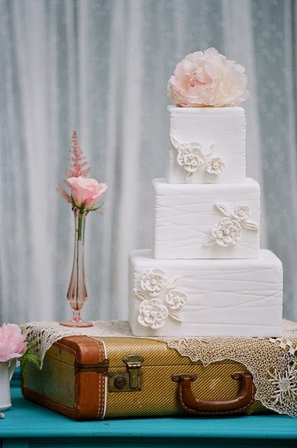 Fancy white cake on a vintage luggage case mixed with light pink flowers - vintage wedding anyone?
