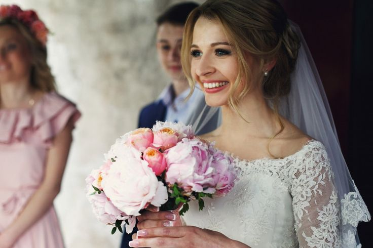 Smiling elegant blonde bride with rose wedding bouquet in white dress and veil