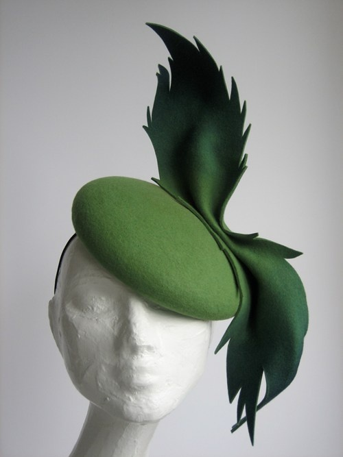 green pillbox with wild swooping trim, designer unknown.