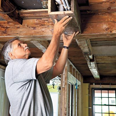 Salvaged sheathing.  Re-purposing old floorboards, subflooring, and sheathing into creating a rustic ceiling look, yet covering exposed beams.  Awesome idea.  Reusing old items.