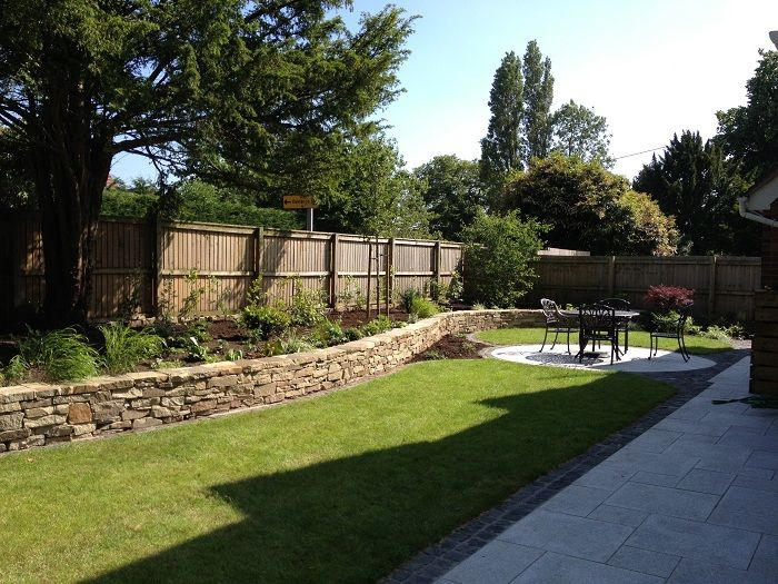 View of part of the 30 metre long natural Cheshire stone raised bed towards another seating area www.ebgardendesign.co.uk