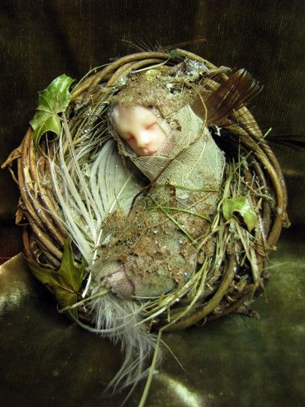 original One-of-a-kind Art Doll Fairy Baby on a nest whose head has been hand-sculpted from polymer clay and painted with Genesis oil paints.   The wigging is made from white mohair.   The body is wire covered with fibers and skeleton leaves.  The nest is made from twigs and dried grass and decorated with, feathers, dried ivy leaves, and glitter. The nest measures 2.5 inches (6.5 cm) in diameter.