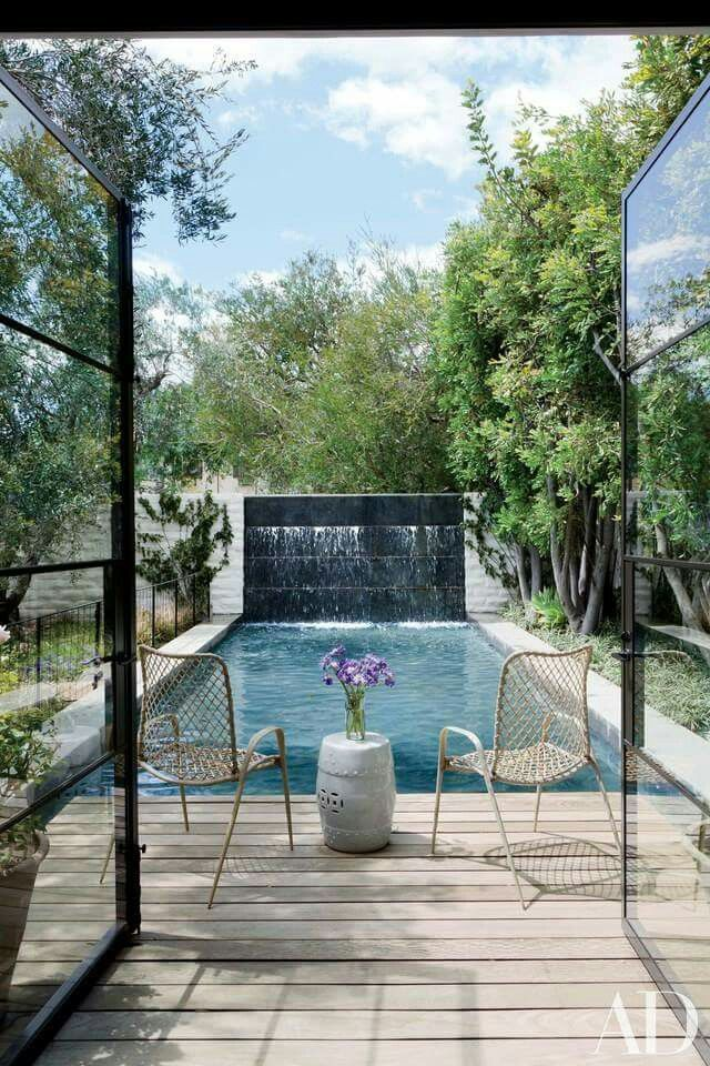French doors lead to rectangular pool with sight line to beautiful wall fountain.