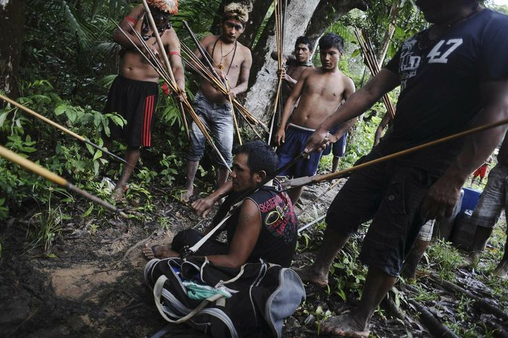 Munduruku Indian warriors stand guard over an illegal gold miner who was detained by a group of warriors searching out illegal gold mines an...