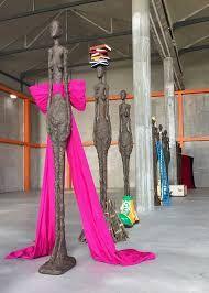 """There is an ironic re-visiting of 1950s glamour with a Marilyn-style dress with a large pink bow – but literally nailed to the ground - allungare le sculture in piedi di Giacometti e vestirle con degli abiti"""".  C'è la rivisitazione glamour anni 50 con Marylin fiocco rosa –  Giovanna d'Arco al rogo che porta orgogliosa sulla testa libri,  """"donna cartesiana"""" che 'indossa' un hula hoop, una moderna viaggiatrice con trench alla Humphrey Bogart e valigie (Prada?)"""