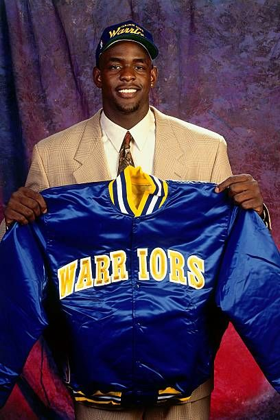 Chris Webber holds a Golden State Warriors jacket after being drafted as the overall draft pick by the Orlando Magic and whose rights later were...