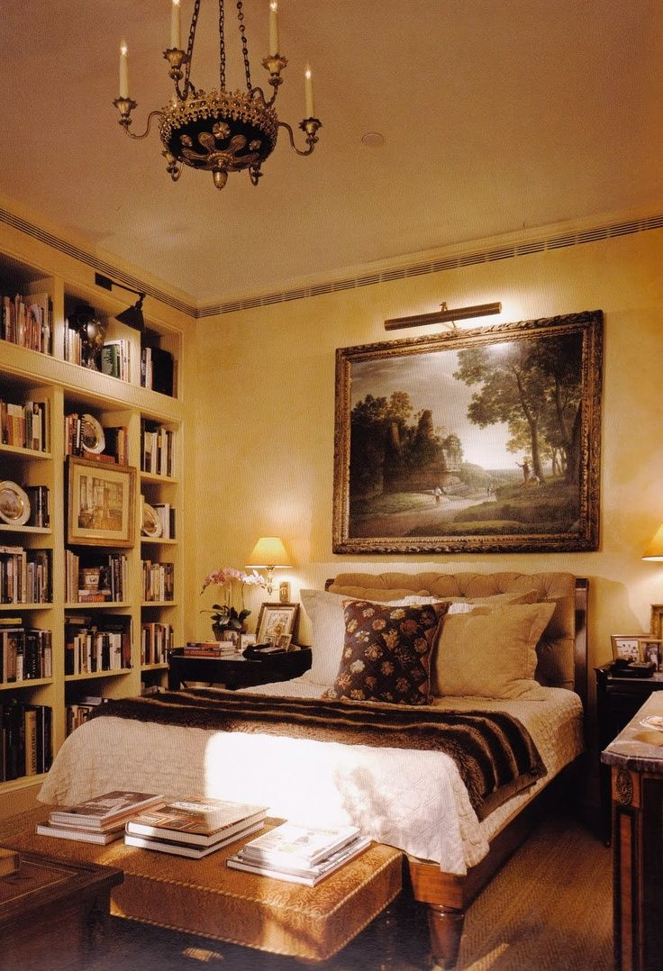 Charlotte Moss designed small bedroom with yellow walls and a wall of books.