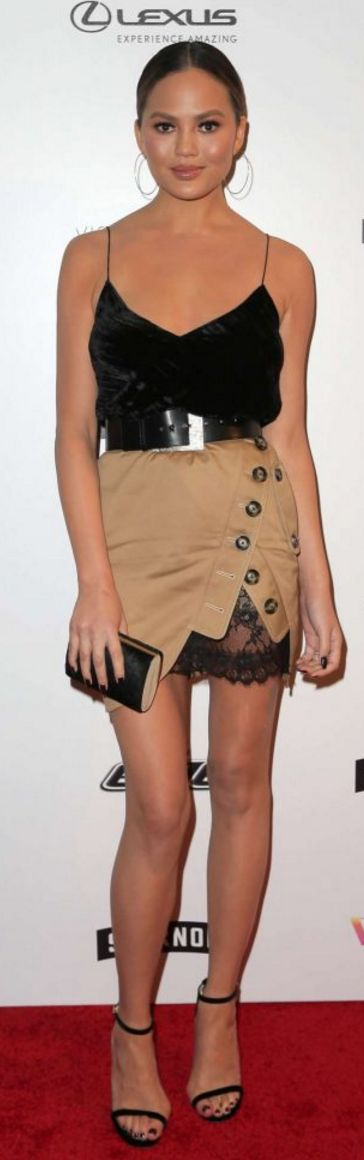 Who made Chrissy Teigan's black clutch handbag, tan button skirt, and ankle strap sandals?