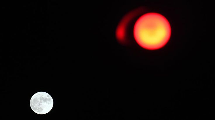 A full moon is seen next to a red traffic light on December 6, 2014 in the western French city of Rennes. (DAMIEN MEYER/AFP/Getty Images)