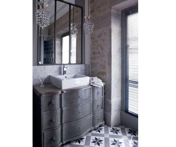 Look rétro dans la salle de bain avec carrelage sol en carreaux de ciment gris. Sublimé par la commode customisée pour recevoir la vasque de lavabo il donne du relief aux murs béton brut.