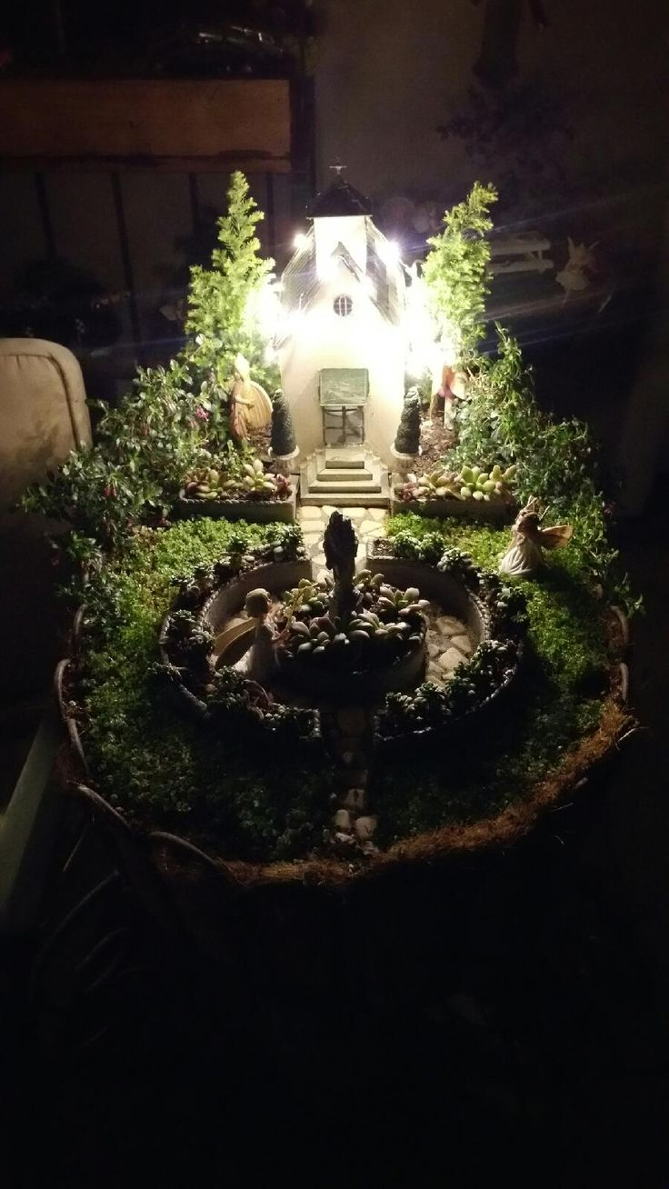 Miniature Fairy Garden - IN AWE as the Christian Village Church is decorated for Christmas with miniature white lights. The girl fairies are in awe of the statue of the Blessed Mother and Baby. 11/2015