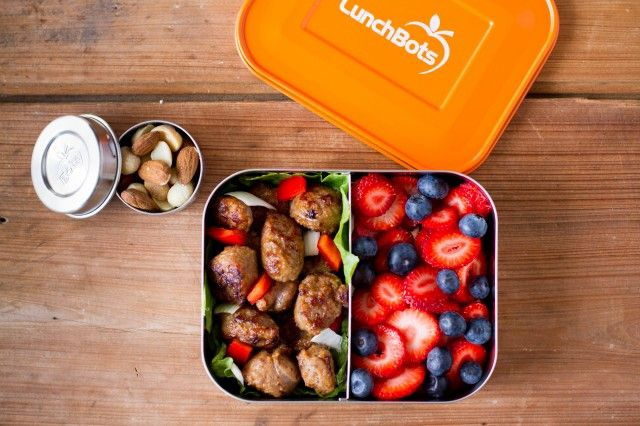 Grilled chicken with vegetables, strawberries, and blueberries in the LunchBots Duo and mixed nuts including almonds, macadamia nuts, and cashews in the LunchBots Dips.