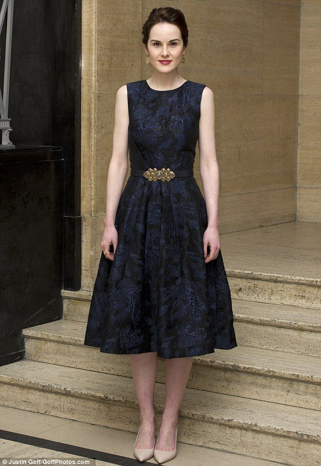 Michelle Dockery went for a Fifties-style navy and black dress with gold belt and matching earrings